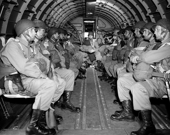 Photo:  American paratroopers, heavily armed, sit inside a military plane as they soar over the English Channel en route to the Normandy French coast for the Allied D