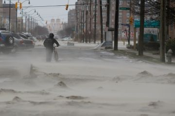 Photo:  A man walks down a street covered in beach sand due to flooding from Hurricane Sandy in Long Beach, New York