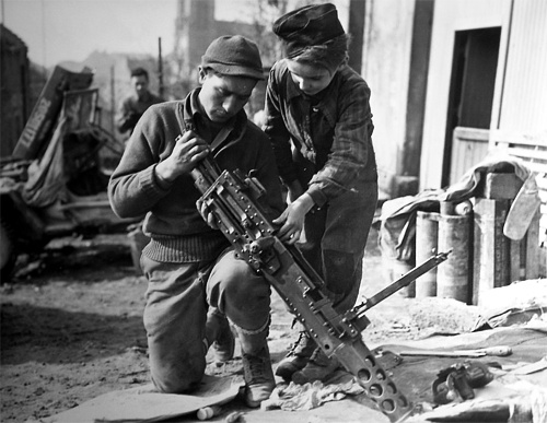Photo:  A young French boy helps a machine gunner in Etzling, France