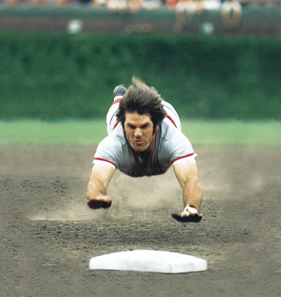 Photo:  Pete Rose dives into third base during a 1975 game between the Cubs and Reds